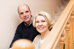 Happy spouses leaning against stairway Stock Photo