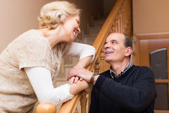 Happy spouses leaning against stairway Stock Photography