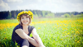 Happy spring. Young happy woman with wreath of dandelion
