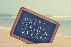 Happy spring break in a blackboard on the beach, with a filter e. The text happy spring break written in a blackboard on the sand of a beach, with a filter royalty free stock photos
