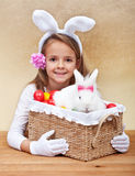 Happy spring girl with easter basket. Holding colorful eggs and white rabbit Stock Images