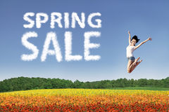 Happy spring sale. Beautiful woman is jumping over colorful flowers during spring sale Royalty Free Stock Image