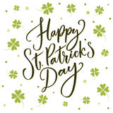 Happy St. Partick`s day greeting. Calligraphy design for cards. Typography on white background with green four-leaf Stock Image