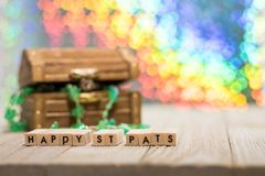 Happy St. Pat`s Day fun rainbow background and treasure chest. Happy St. Patrick`s Day fun rainbow background on wooden board with treasure chest and shamrock royalty free stock photo