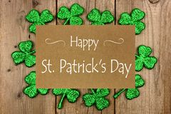 Happy St Patrick Day greeting card with shiny shamrocks over rustic wood stock photo