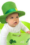 Happy St. Patrick's Day. Adorable baby boy wearing a St. Patrick's Day hat sitting in a green bucket with shamrocks Stock Photos