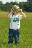 Happy St. Patrick's Day. Adorable little girl in shamrock sunglasses Royalty Free Stock Photos