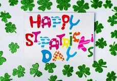 Happy St. Patrick& x27;s Day card with shiny clovers. Flat lay Stock Images