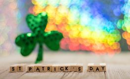 Happy St. Patrick`s Day fun rainbow background. On wooden board with treasure chest and shamrock and gold coins, selective focus, shallow DOF royalty free stock image