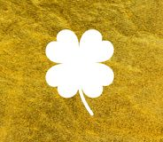 Happy St. Patrick`s Day 17 march. Clover with four leaves White on golden backround Stock Photos