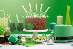 St Patrick`s Day Party Table with Chocolate Cake, Leprechaun Hat and Lens Flare. Happy St Patrick`s Day, March 17, green and white party table with showstopper Royalty Free Stock Photography