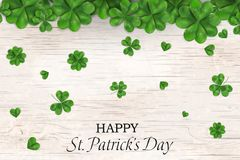 Happy St. Patrick`s day. st patricks day design with falling shamrock, four leaved clover on wooden background. Ireland. Symbol pattern. Design for banner, card Stock Images