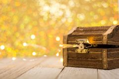 Treasure Chest on wooden board with beautiful gold bokeh room for text. Happy St. Patrick`s Day treasure chest and gold background on wooden board, selective royalty free stock photos