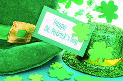 Happy St Patricks Day. Happy St Patrick's Day tag with party hats and shamrocks over white Royalty Free Stock Images