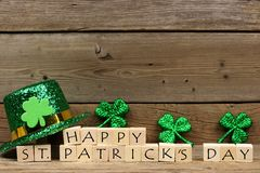 Happy St Patricks Day blocks with shamrocks and leprechaun hat. Happy St Patricks Day wooden blocks with shiny shamrocks and leprechaun hat on a wooden Stock Photo