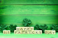 Happy St Patricks Day blocks with shamrocks over green wood Stock Photo