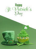 Happy St Patricks Day green cupcake with ssample text - vertical. Happy St Patricks Day green cupcake with shamrock flags with leprechaun hat against green and Stock Photos