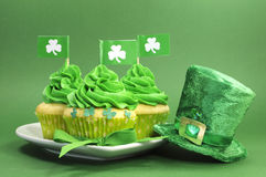 Happy St Patricks Day green cupcakes on green background. Happy St Patricks Day green cupcakes with shamrock flags and leprechaun hat against a green background Royalty Free Stock Images