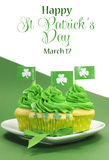 Happy St Patricks Day green cupcakes with shamrock flags. On green and white background with sample text or copy space for your text here Stock Photo