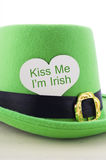Happy St Patricks Day green leprechaun hat. On white wood table with Kiss Me I am Irish heart shape greeting sign, vertical Royalty Free Stock Photo