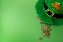 Happy St Patricks Day leprechaun hat with gold coins on green background. Top view. Happy St Patricks Day leprechaun hat with gold coins on green background Royalty Free Stock Photography