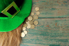 Happy St Patricks Day leprechaun hat with gold coins on green wood background. Top view Stock Photos