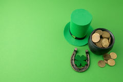 Happy St Patricks Day leprechaun hat with gold coins and lucky charms on green background. Top view. Royalty Free Stock Photography