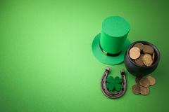 Happy St Patricks Day leprechaun hat with gold coins and lucky charms on green background. Top view. Royalty Free Stock Photo