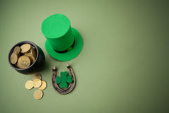 Happy St Patricks Day leprechaun hat with gold coins and lucky charms on green background. Top view. Royalty Free Stock Photos