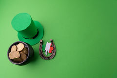 Happy St Patricks Day leprechaun hat with gold coins and lucky charms on green background. Top view. Royalty Free Stock Images
