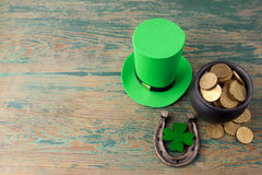 Happy St Patricks Day leprechaun hat with gold coins and lucky charms on vintage style green wood background. Top view Stock Photo