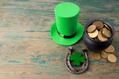 Happy St Patricks Day leprechaun hat with gold coins and lucky charms on vintage style green wood background. Top view Royalty Free Stock Images
