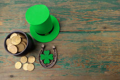 Happy St Patricks Day leprechaun hat with gold coins and lucky charms on vintage style green wood background. Top view. Happy St Patricks Day leprechaun hat with Royalty Free Stock Photos