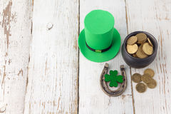 Happy St Patricks Day leprechaun hat with gold coins and lucky charms on vintage style white wood background. Top view. Happy St Patricks Day leprechaun hat with Stock Photo