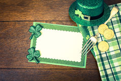 Happy St. Patricks Day Menu or Invite Card with Shamrocks, Hat, Lucky Coins, Napkins and fork from top down view with blank area Royalty Free Stock Photos