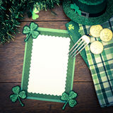 Happy St. Patricks Day Menu or Invite Card with Shamrocks, Hat,. Lucky Coins, Napkins and fork from top down view with blank room or space for copy, text, your Royalty Free Stock Photos