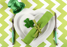 Happy St Patricks Day table place setting. With heart shape plates, shamrock cookie and leprechaun hat on green and white chevron stripe table Stock Photo
