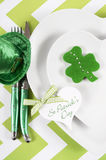 Happy St Patricks Day table place setting. With heart shape plates, shamrock cookie and leprechaun hat on green and white chevron stripe table, vertical Royalty Free Stock Photo
