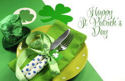 Happy St Patricks Day table setting with shamrocks and leprechaun hat and sample text. Greeting, on green and white background Royalty Free Stock Image