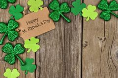 Happy St Patricks Day tag with shamrock corner border. Happy St Patricks Day tag with corner border of shiny shamrocks over a rustic wood background royalty free stock images