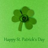 Happy St Patricks Day text with shamrock. Happy St Patrick Day text with handmade shamrock on a green paper background Royalty Free Stock Image