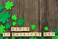 Happy St Patricks Day wooden blocks with shamrocks over wood. Happy St Patricks Day wooden blocks with corner border of shamrocks over a rustic wooden background royalty free stock image