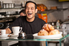 Happy staff at restaurant. A staff at restaurant bursts out with laughter for a joke cracked by customer Stock Image