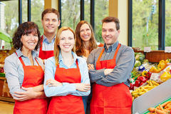 Happy staff team in supermarket Stock Photo