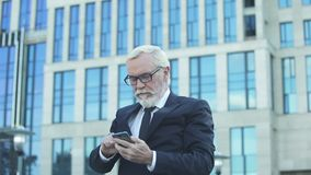 Happy stock market broker reading news on phone checking indices in business app. Stock footage stock video