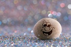 The happy stone emoji. Emotions on color glitter boke background stock photos