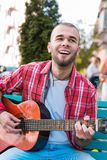 Happy street musician expressing feelings though song. Song writer. Joyful street musician singing and using guitar on street royalty free stock photos