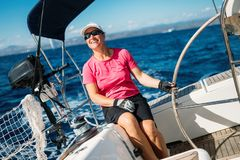 Happy strong woman sailing with her boat stock photography