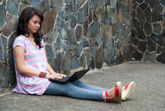 Happy student. A female student is studying with her laptop in university's park Stock Photography