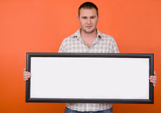 Happy student with banner. Casual guy standing with banner on orange background Royalty Free Stock Photography